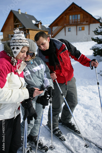 Ski teenagers looking at a phone