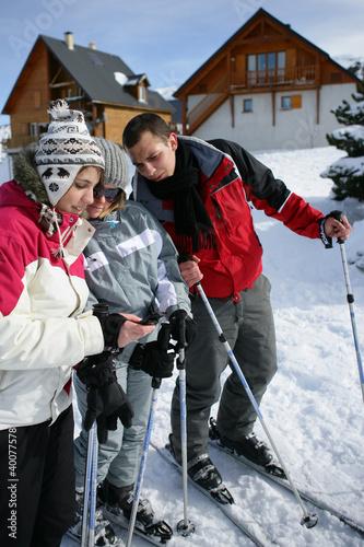 Ski teenagers looking at a phone