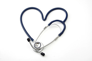 A stethoscope lying in a shape of a heart on white background