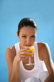Brunette drinking orange juice from wine glass