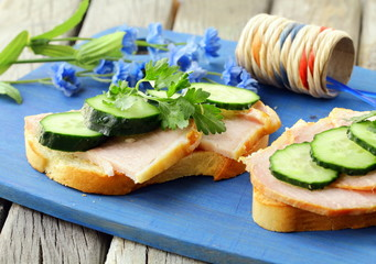 Sandwich with ham and  cucumber  on the wooden cutting board