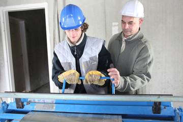 Two men operating machine than cuts sheet metal