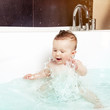 Cute baby splashing water while taking a bath