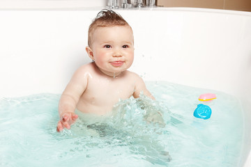Cute baby having fun and smiling while taking a bath