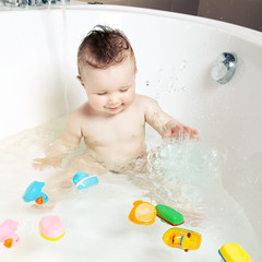 Cute smiling baby splashing water while taking a bath