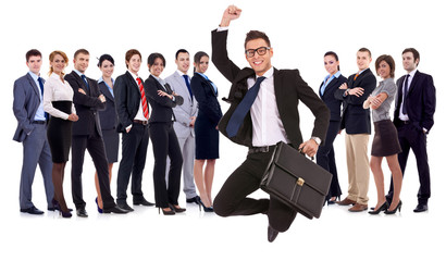 business man holding briefcase jumping in front of his team