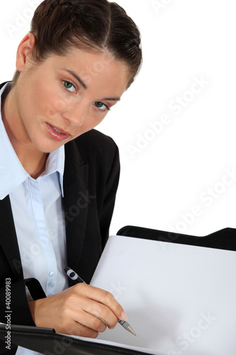 Businesswoman holding pen and folder