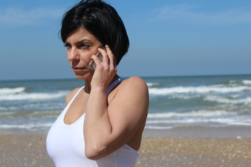 Pretty woman talking on her mobile phone, at the beach