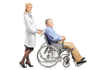 Nurse or doctor pushing a handicapped senior man in a wheelchair