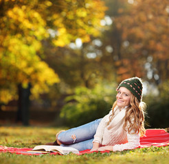 Young smiling female reading a book in a park