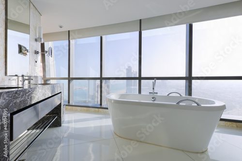 Luxury bathroom with stand alone tub near windows in a skyscrape