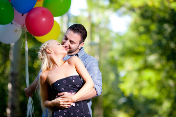young loving couple with balloons on natural background