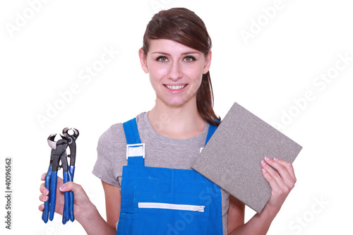 Woman holding tile and tile cutter