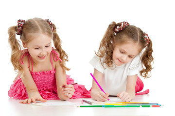 schoolgirls drawing with color pencils together over white backg
