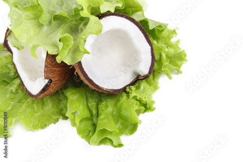 Cracked coconut on green leaf isolated on white