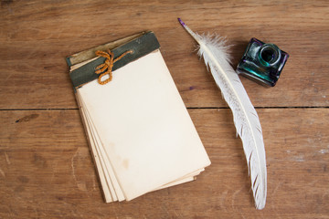 Quill ink pen and inkwell, old notepad on oak wood table