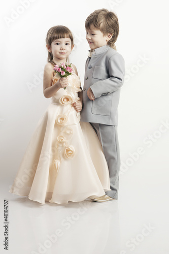 Two beautiful little boys and girls in wedding dresses