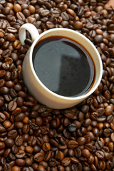 A cup of coffee surrounded by coffee grains - view above