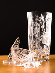shards of broken vase lying next to another vase