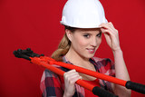 craftswoman holding spanner against red background