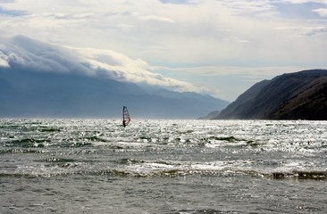 Windsurfer on a sea with mountains and clouds