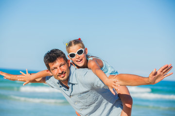 Father and his daughter having fun on beach