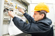 Leinwanddruck Bild - Electrician with drawing at power line box