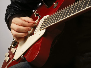 Close-up of a guitar and playing hands, isolated on grey