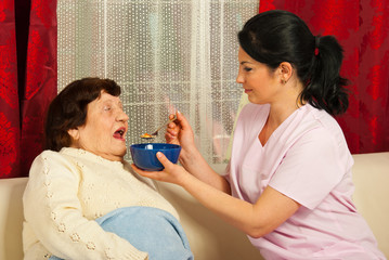 Nurse giving soup to elderly woman