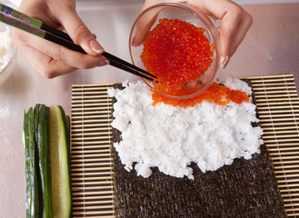 cook making   sushi rolls  with caviar