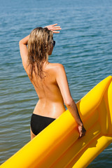 Summer woman by sea water floating mattress