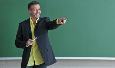 Lehrer steht vor der Schultafel.