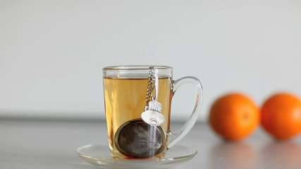 cup of strong black tea biscuit and two orange