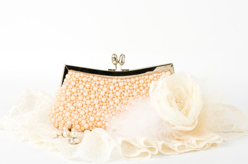 Fashionable handbag with pearls and laces on white background.