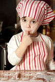 Fototapety little chef in the kitchen wearing an apron and headscarf