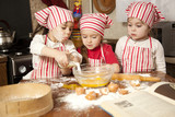 Three little chefs enjoying in the kitchen making big mess. Litt - 40120913