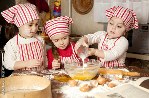 Foto op Canvas Koken Three little chefs enjoying in the kitchen making big mess. Litt