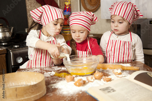 Three little chefs enjoying in the kitchen making big mess. Litt - 40120913