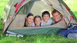 Family smiling while lying in a tent