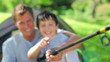Happy father and son holding a fishing rod