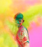 Holi celebrations in India. Closeup of a boy playing Holi