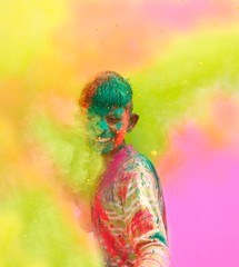 Holi celebrations in India. Closeup of a boy playing Holi