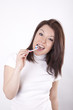 Attractive young woman enjoys cleaning her teeth