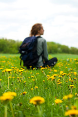 Woman traveler with a backpack sitting among field with dandelio