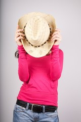 pink lady hidding her face with straw hat
