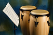 Two congas on colored background with music stand and sheet