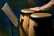Unrecognizable musician playing congas with music stand