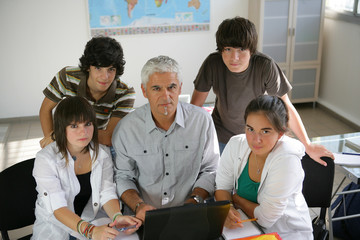 Pupils with their teacher and a laptop