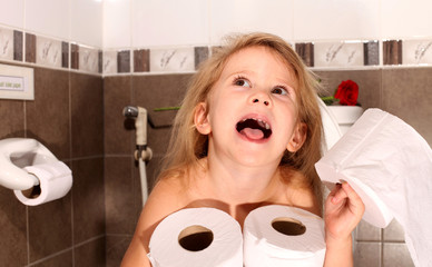 child with a roll of toilet paper sitting on the toilet