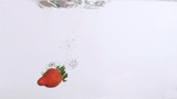 Red fruit in super slow motion falling in the water